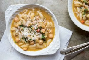Two white bowls filled with chickpea and cavatelli soup on white napkin with spoons.