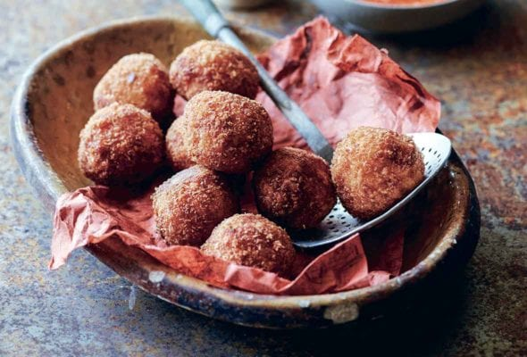 A large bowl filled with fried arancini balls and a small bowl of red pepper sauce on the side