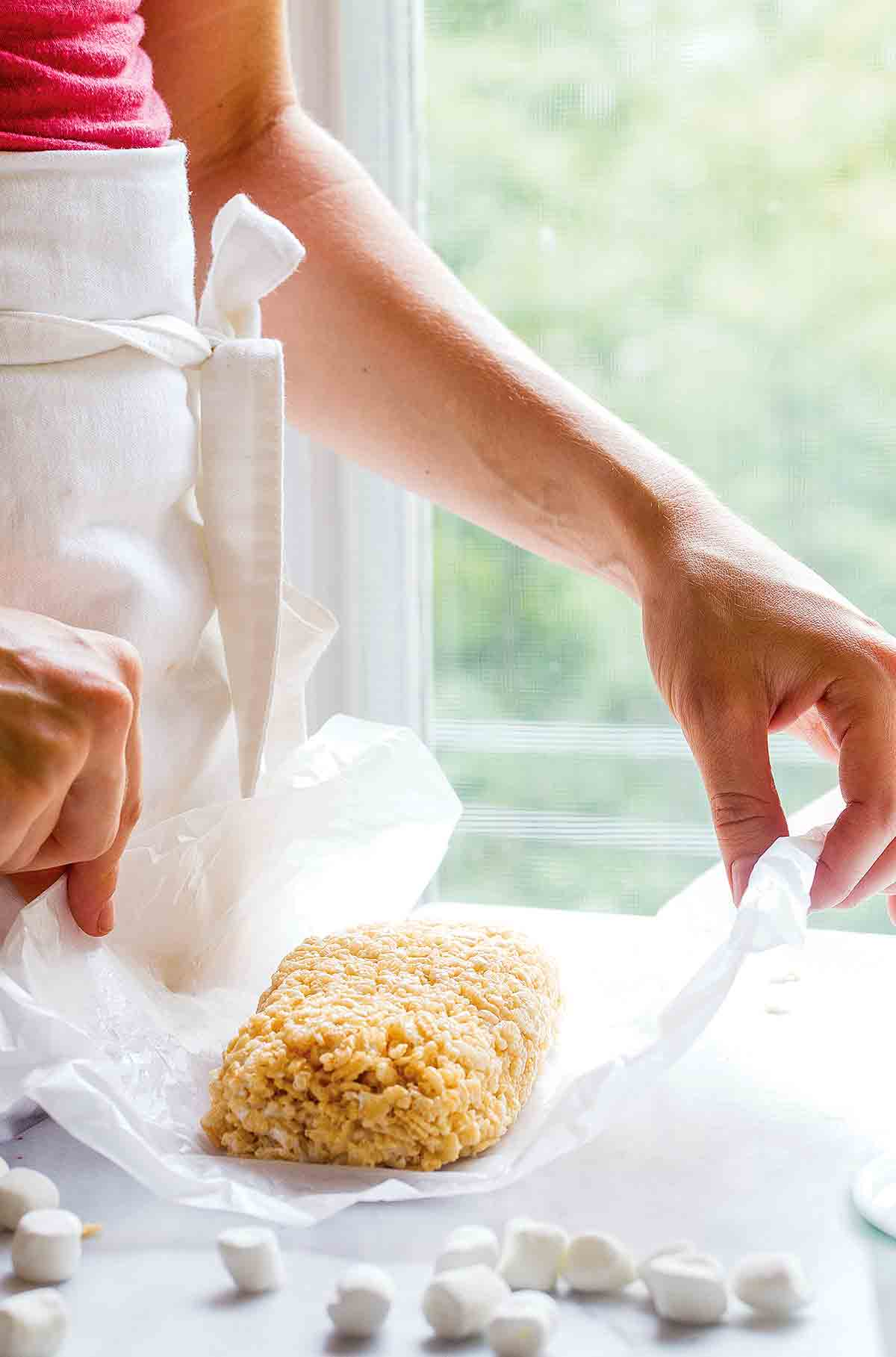 A woman holding a small batch of Rice Krispies treats for two on a piece of wax paper.