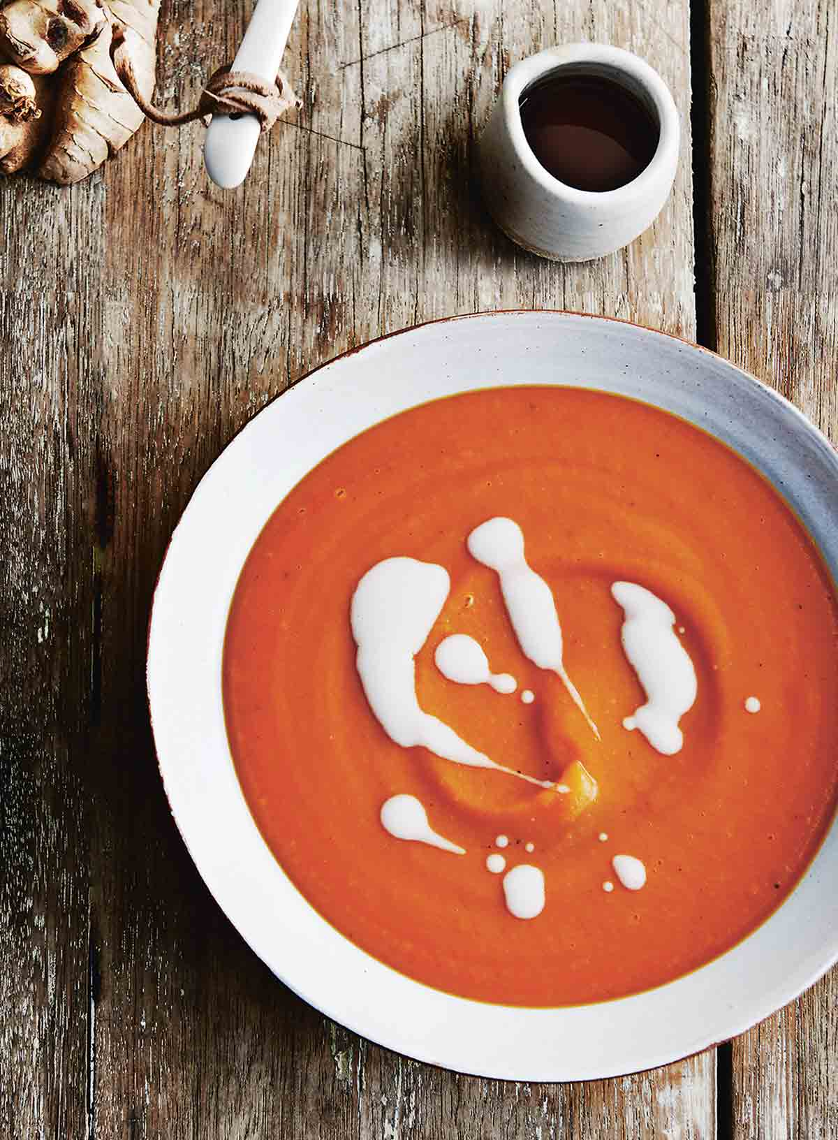 A white earthenware bowl of sweet potato soup with coconut milk drizzled over the top.