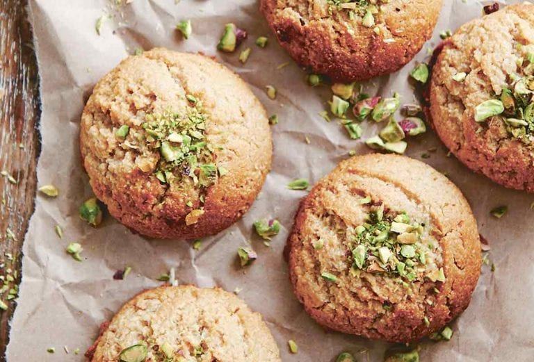 Six tahini cookies on a piece of parchment with chopped pistachios on the cookies and on the parchment.