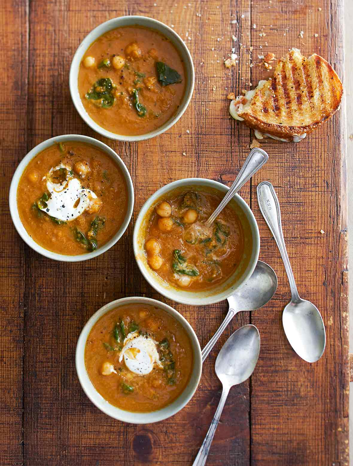 Four bowls of tomato soup with chickpeas and spinach, two with dollops of sour cream, and a half eaten grilled cheese on the side.