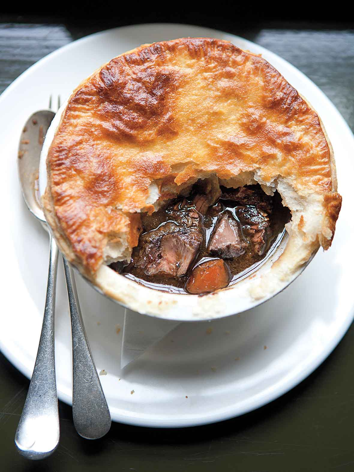 A venison pie with part of the crust missing on a white plate with a fork and spoon beside it.