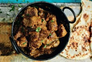 A black pot filled with chunks of beef Raj curry, topped with cilantro, nearby is roti Indian bread