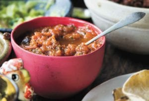 A red bowl filled with fire-roasted salsa in the middle of a Mexican feast.