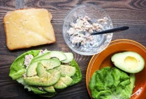 A slice of whole grain bread topped with gruyere cheese, a bowl with tuna salad, and a butter lettuce leaf topped with tuna salad, avocado, and pepper