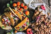 A black platter with several grilled chicken tacos with fruit salsa, a few cherry tomatoes, and a wooden board with cut chicken, halved plums, and queso fresco.