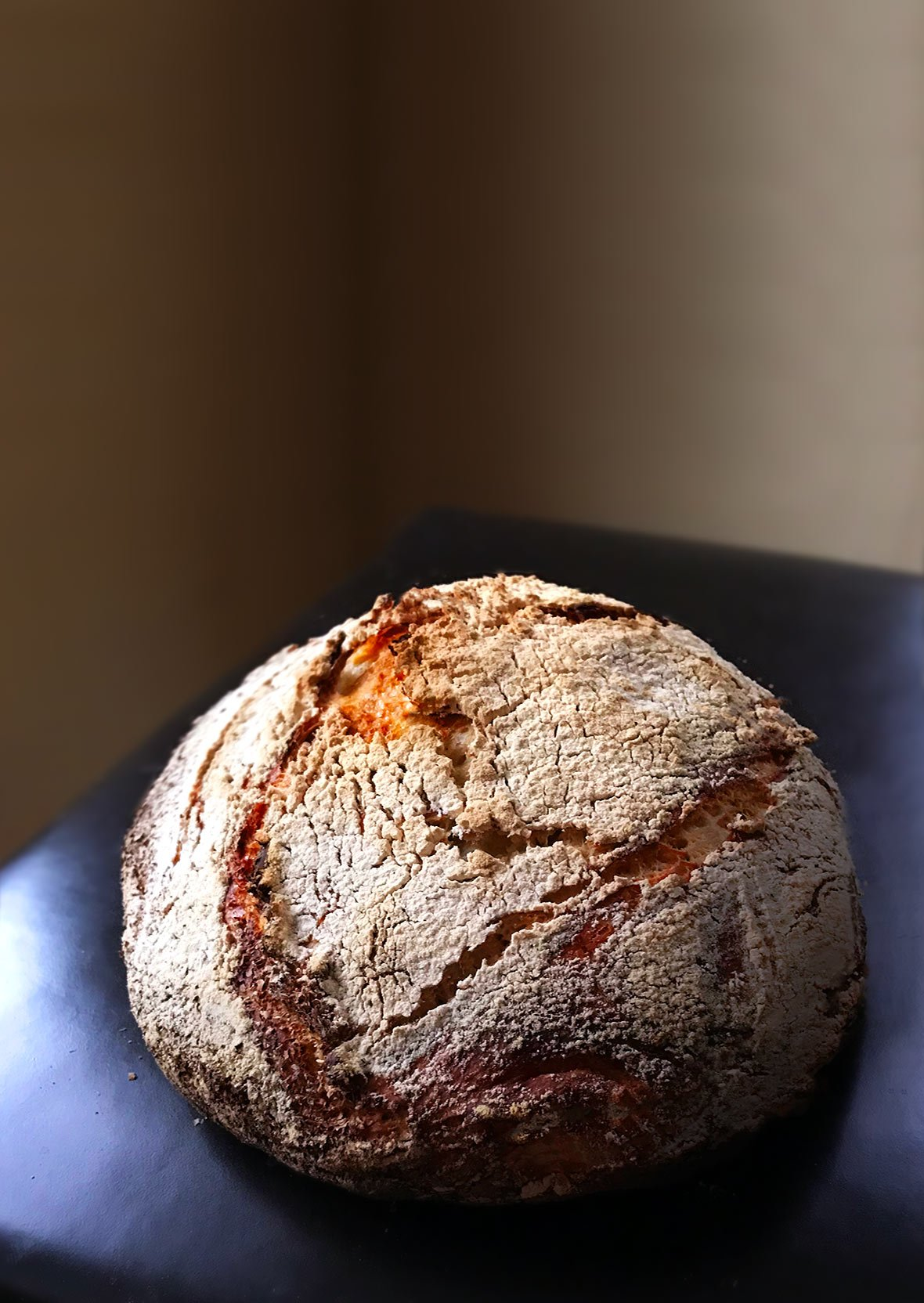 A round loaf of Jim Lahey's no-knead bread, dusted with flour on a leather chair