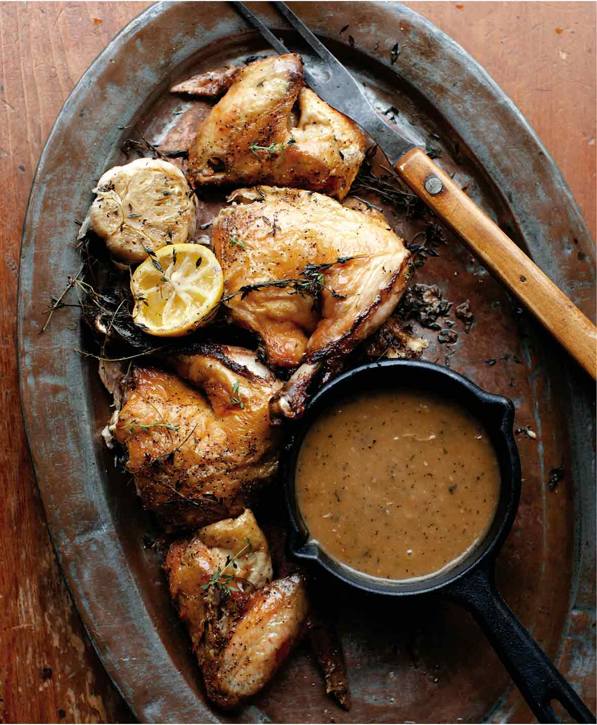 Pieces of roast chicken wth a small dish of pan gravy and a halved lemon and bulb of garlic on an oval metal tray.
