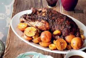 A white oval platter holding a whole roast duck with clementines scattered around it.