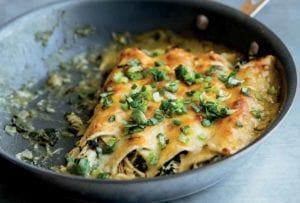A non-stick skillet with four skillet enchiladas in it, topped with scallions, and a spatula resting beside the skillet.