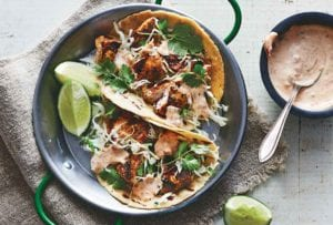 Two ancho fish tacos in a metal dish with lime wedges and chipotle mayo on the side.