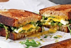 An asparagus and fried egg panini with arugula and Tallegio cheese sliced in half in parchment paper