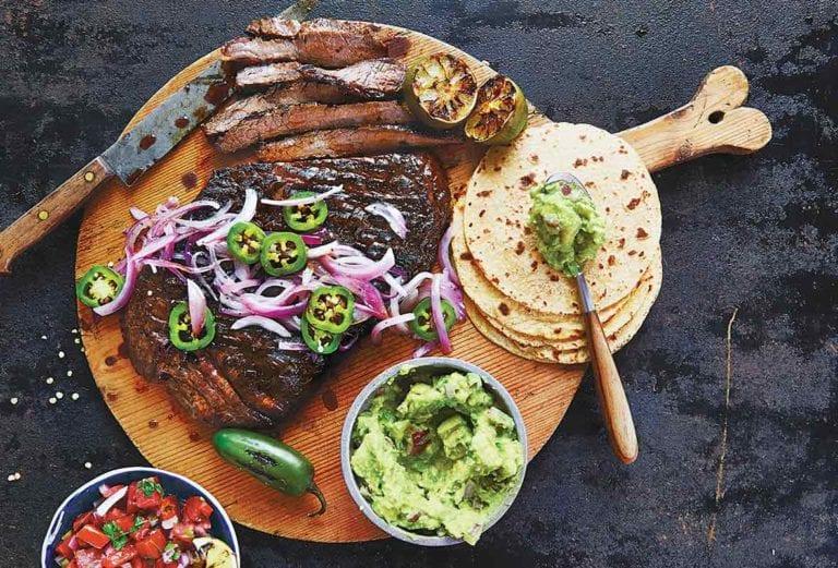 The makings of beef fajitas on a wooden board - tortillas, steak, guacamole, salsa.