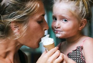 A mother and daughter sharing a mint chocolate chunk ice cream cone.