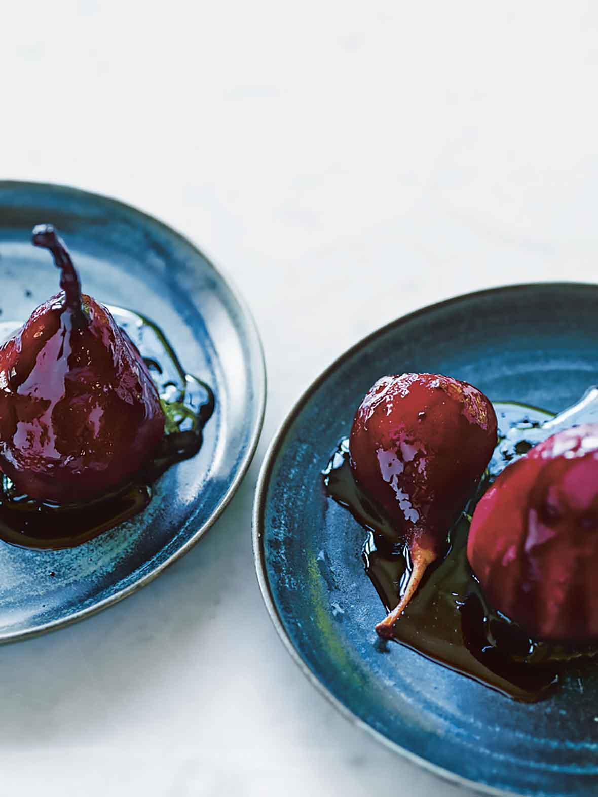 Two blue plates with red wine poached pears and a drizzle of sauce over them.