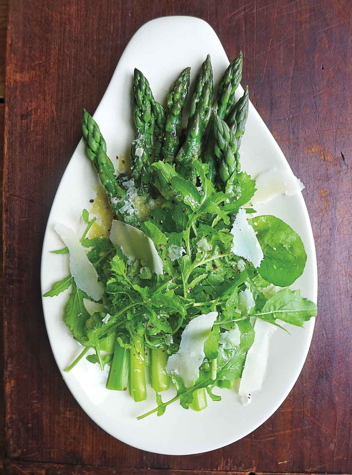 An asparagus and arugula salad topped with Parmesan on a teardrop-shaped plate.