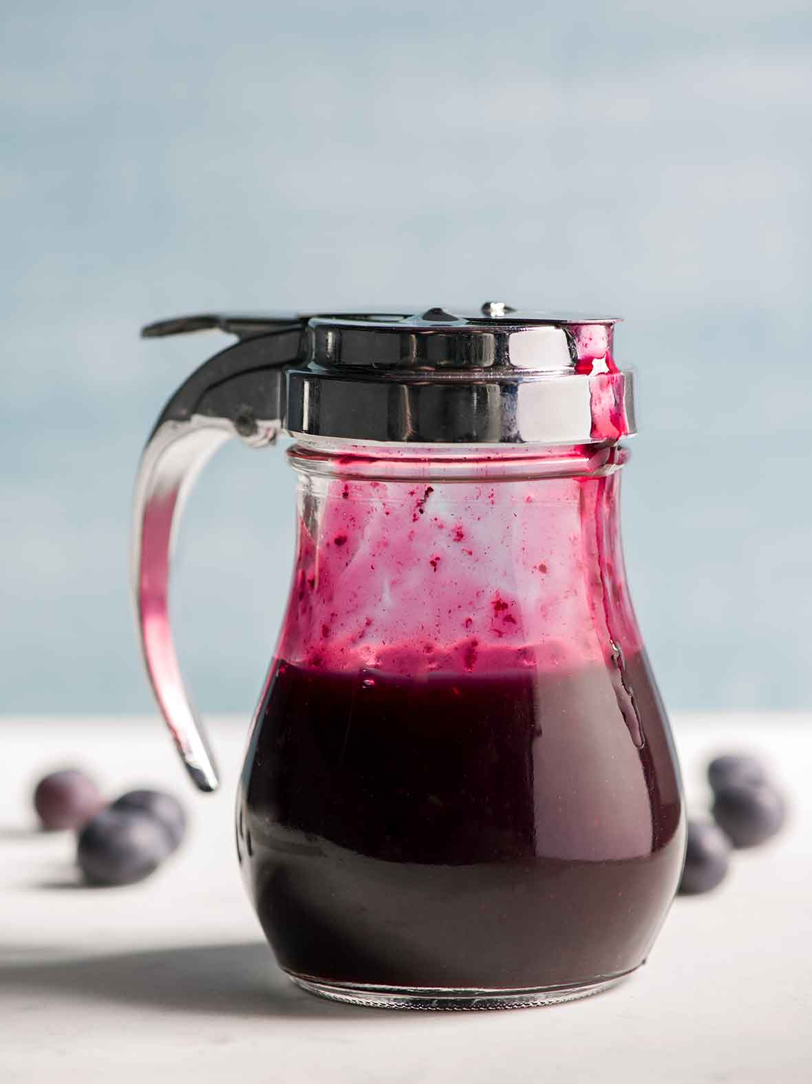 A diner-style dispenser half-filled with blueberry syrup.