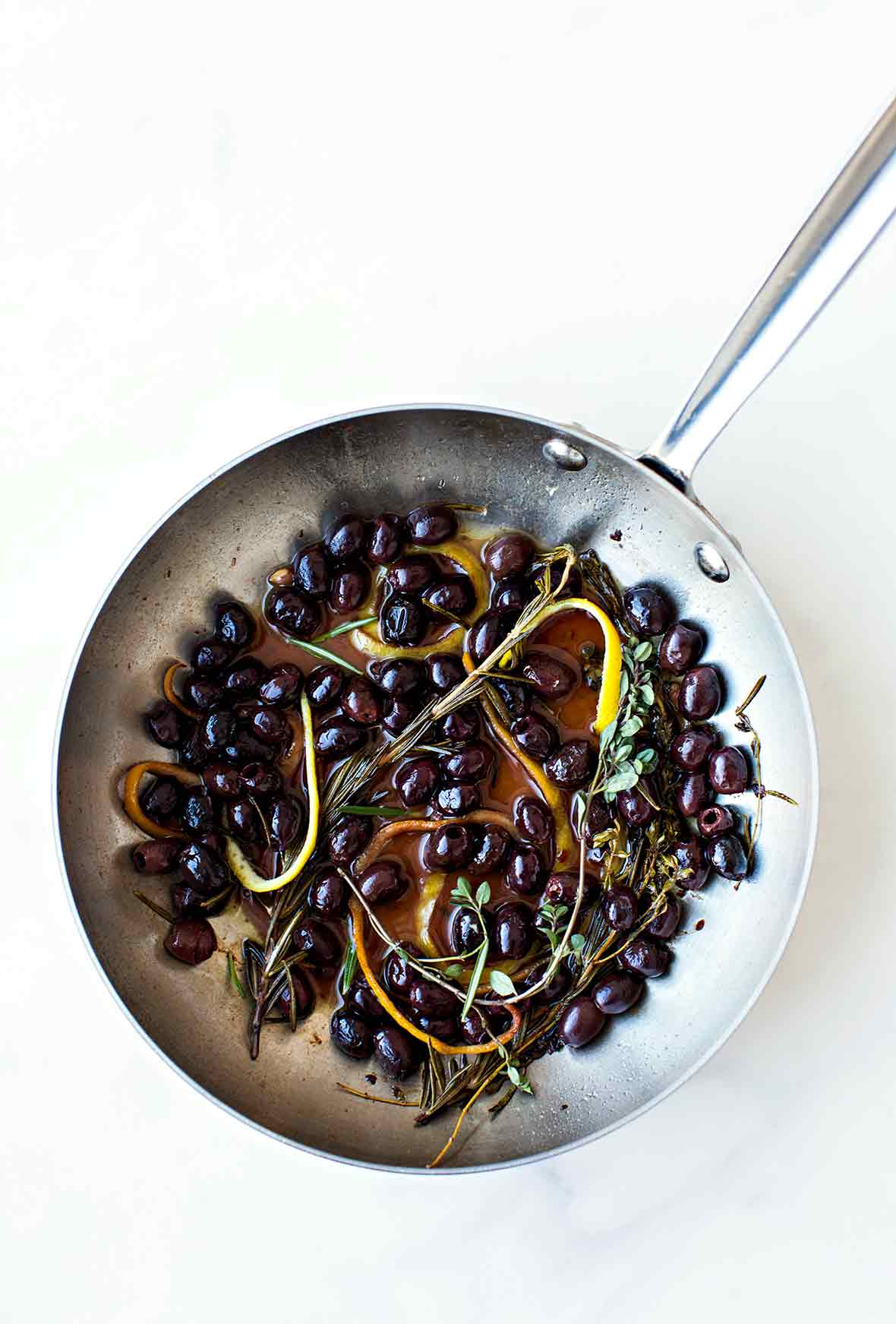A skillet filled with black olives in an infusion of herbs and lemon and orange peel