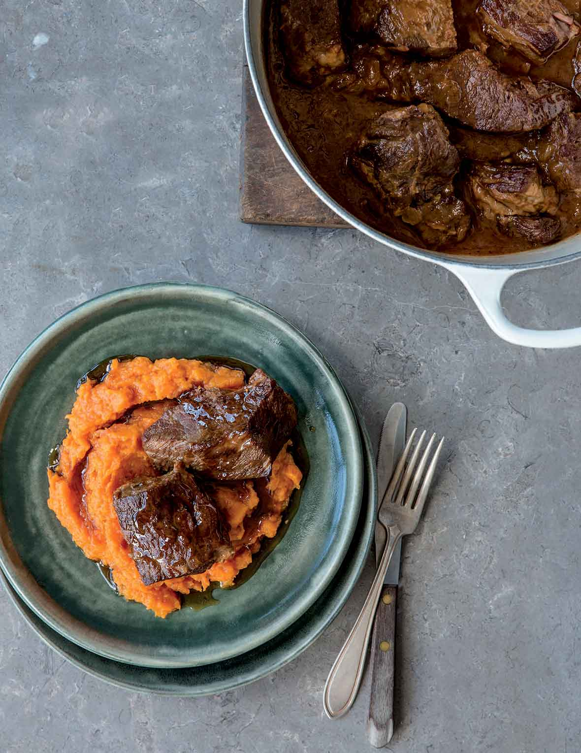 A green plate containing sweet potato puree, topped with 2 pieces of short rib. A Dutch oven is beside the bowl with more short ribs.