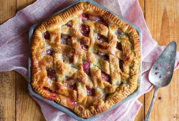 A hexagonal rhubarb pie with a lattice top crust on a pink linen cloth with a pie server resting beside the pie.
