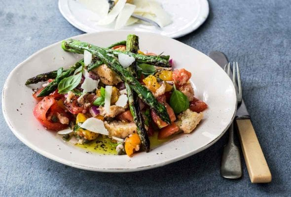 A white plate topped with a spring panzanella made with tomatoes, bread, asparagus, and Parmesan. A small plate of additional shaved Parmesan sits beside it.
