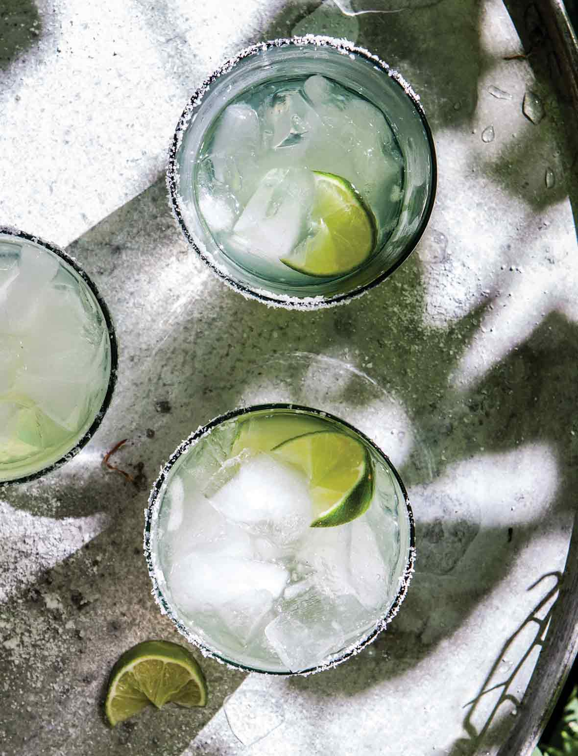 Three glasses of ultimate margarita with lime wedges.