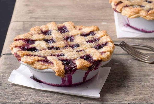 Two individual size blueberry pies on a wooden table.