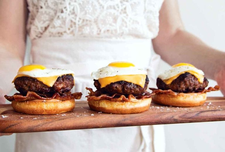 A woman holding a wooden tray with 3 breakfast burgers topped with eggs.