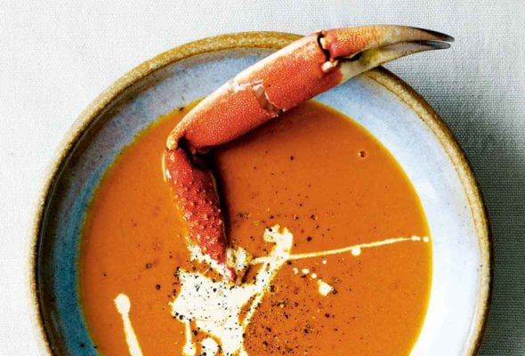 A bowl of creamy crab soup drizzled with cream, and sprinkled with pepper, with a crab leg sticking out of it.