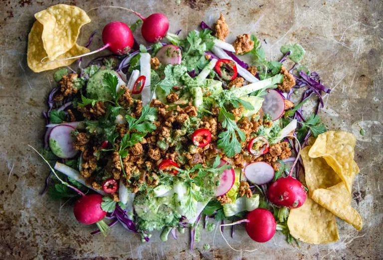 A turkey taco salad, made with ground turkey, radishes, cilantro, and jicama, mounded on a sheet pan.