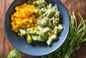 A blue bowl filled with the components of mango guacamole, with a bunch of cilantro, halved limes, and a fork on the side.