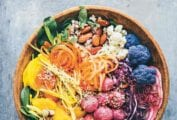 A wooden bowl filled with shredded carrots and red cabbage, purple cauliflower, radishes, broccoli, almonds, and rice