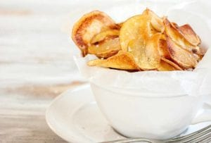 A white bowl filled with salt and vinegar potato chips with a fork resting beside.