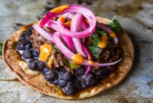 Two shredded beef tostadas topped with beans, beef, and pickled onions.