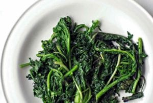 A pile of charred greens--kale and spinach--on a white plate
