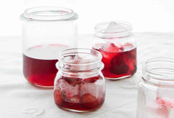 A tall bottle and several small jars filled with strawberry punch and ice cubes.