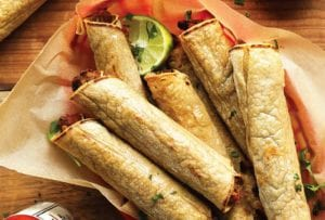 A basket of black bean taquitos with lime halves and hot sauce on the side.