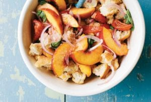 A white bowl filled with tomato and peach panzanella on a blue wooden surface.