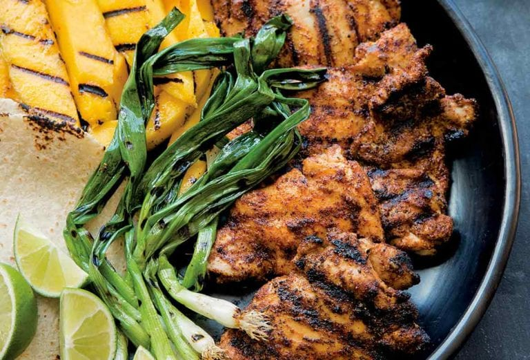 A large platter with grilled mango, chicken, scallions, tortillas, and lime, for grilled chicken tacos.