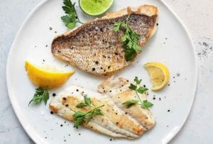 Two pieces of pan-seared fish fillet on a white plate with lemon wedges, a lime half, and parsley, to garnish.