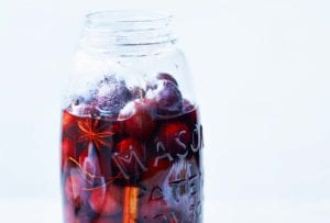A mason jar mostly filled with pickled cherries, pickling liquid, star anise, and a cinnamon stick.
