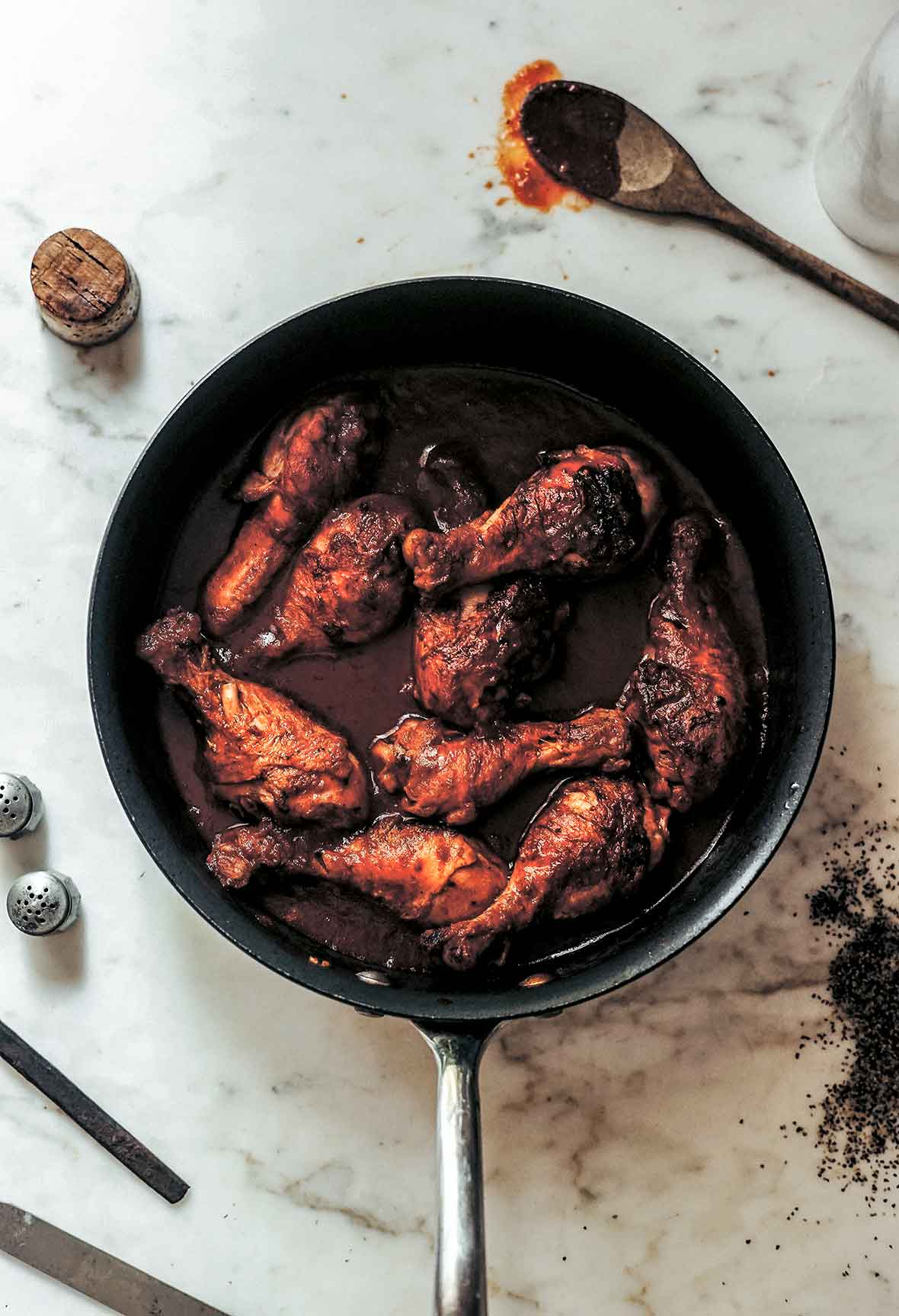 A skillet filled with chicken drumsticks braised in wine with a wooden spoon and wine cork lying beside the skillet.