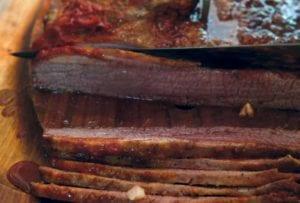 Slices of Nach Waxman's beef brisket on a cutting board