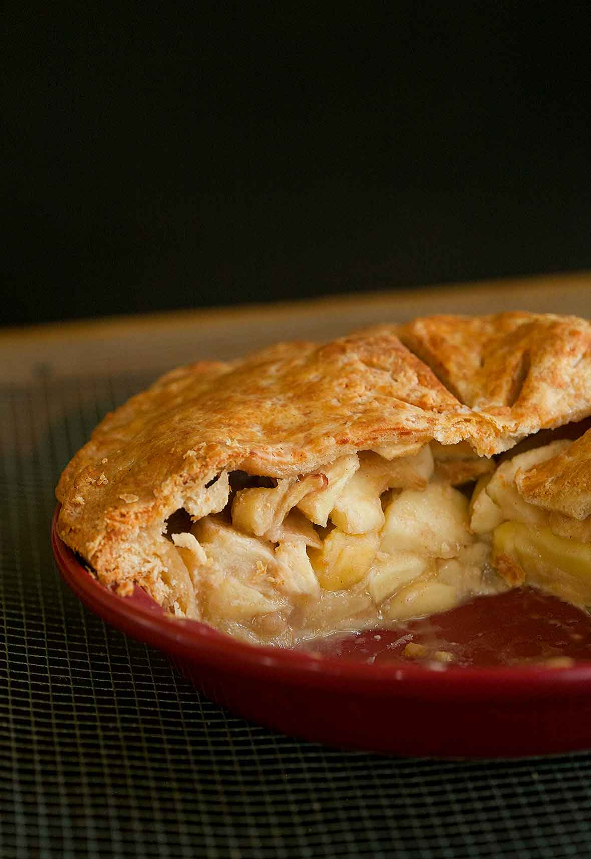 An apple pie with Cheddar crust in a red pie pan cut into to show the Golden Delicious apples inside