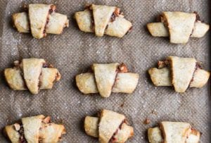 A baking sheet with four rows of baked rugelach