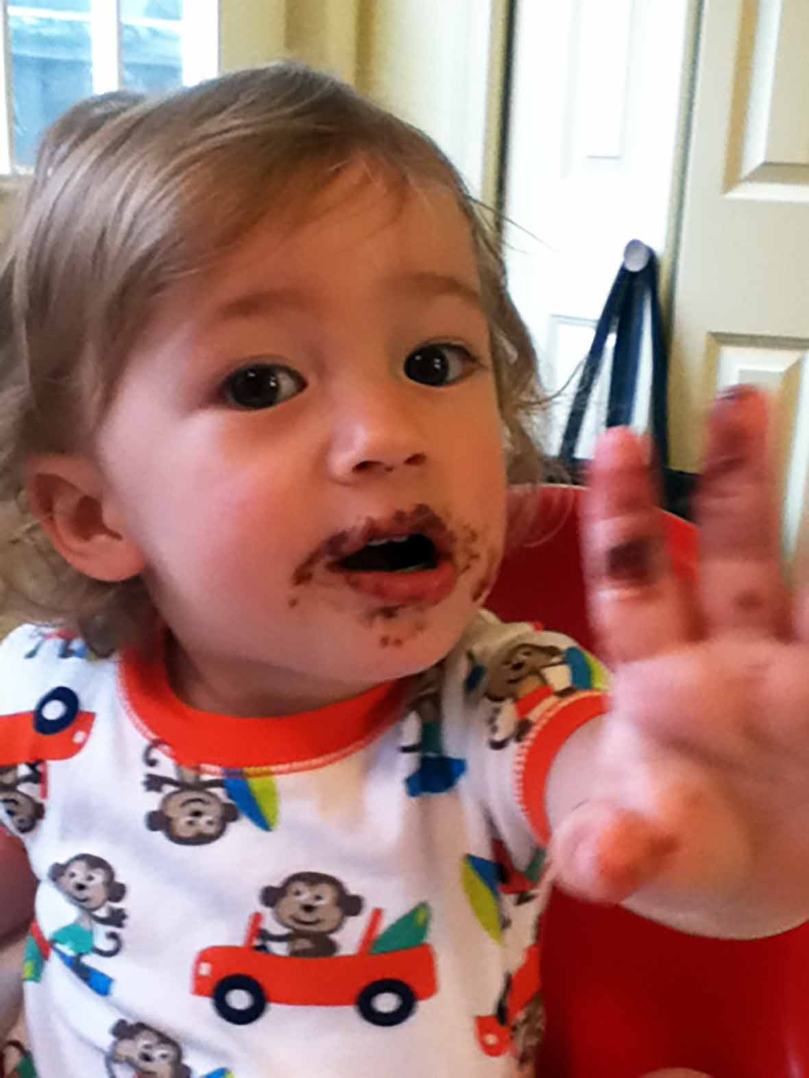An toddler proudly showing his face smeared with Nutella