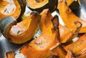 Wedges of roasted pumpkin on a rimmed baking sheet.