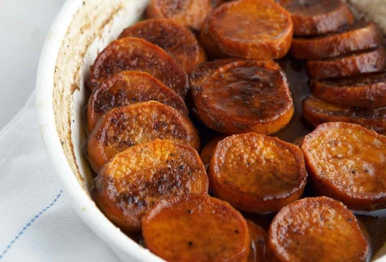A white baking dish filled with slices of cooked sweet potato