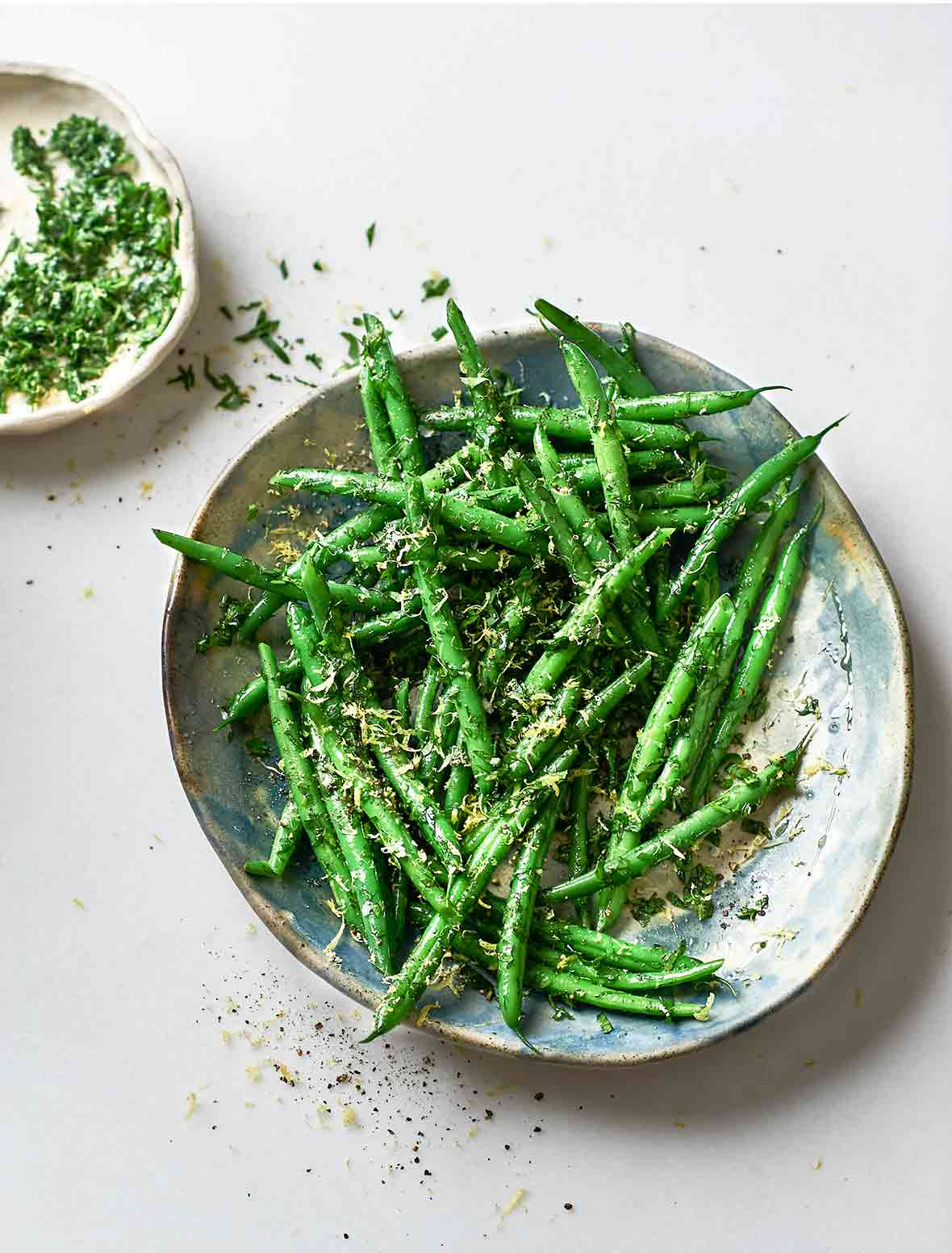 A serving platter piled with green beans and sprinkled with gremolata. A small dish of gremolata sits beside the serving plate.